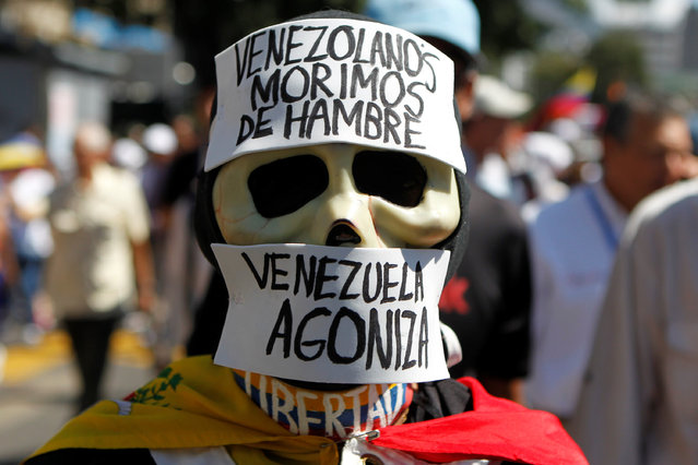 """An opposition supporter wearing a costume that reads """"Venezuelans starve"""" and """"Venezuela agonizes"""", takes part in the rally against Venezuelan President Nicolas Maduro's government and to commemorate the 59th anniversary of the end of the dictatorship of Marcos Perez Jimenez in Caracas, Venezuela January 23, 2017. (Photo by Christian Veron/Reuters)"""