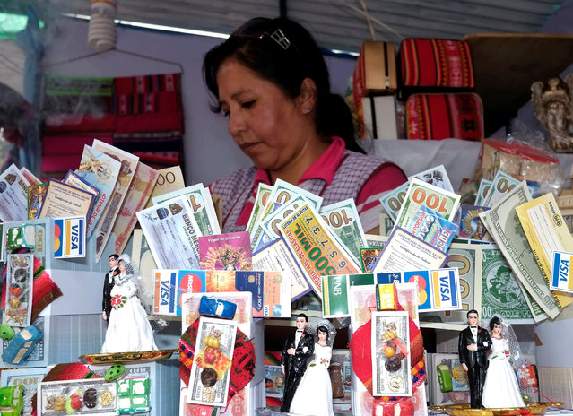 """A woman offers miniature goods during the """"Alasitas"""" fair, where people buy miniature versions of goods they hope to acquire in real life, in La Paz, Bolivia, January 24, 2017. (Photo by David Mercado/Reuters)"""