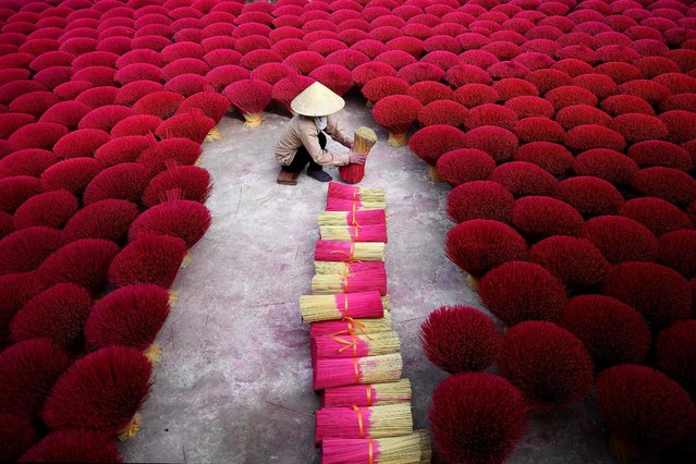 "This picture taken on January 3, 2019 shows a Vietnamese woman collecting incense sticks in a courtyard in the village of Quang Phu Cau on the outskirts of Hanoi. In Vietnam's ""incense village"", hundreds of workers are hard at work dying, drying and whittling down bamboo bark to make the fragrant sticks ahead of the busy lunar new year holiday. (Photo by Manan Vatsyayana/AFP Photo)"