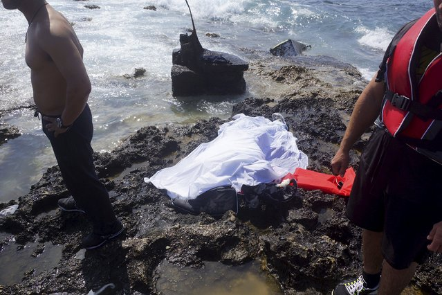 People stand next to the recovered body of a migrant, who tried to reach Greece, at the coast of the southeastern island of Rhodes April 20, 2015. (Photo by Michalis Loizos/Reuters)