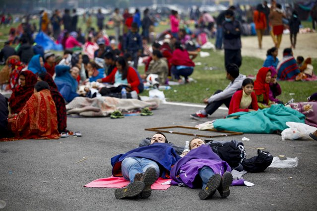 In this photo provided by China's Xinhua News Agency, tourists sleep at an open space after an earthquake in Kathmandu, Nepal, Saturday, April 26, 2015. Planeloads of aid material, doctors and relief workers from neighboring countries began arriving Sunday in Nepal, a poor Himalayan nation reeling from a powerful earthquake that destroyed infrastructure, homes and historical buildings. (Photo by Pratap Thapa/Xinhua via AP Photo)