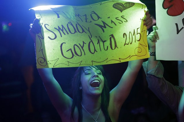 "A fan of a contestant cheers holding a poster with a message of support that reads in Spanish; ""Strength Smady Viveros"" during the fourth edition of the ""Miss Gordita"" beauty contest in Asuncion, Paraguay, Saturday, April 25, 2015. In a country in which 57% of the population is obese according to the Ministry of Health, it's not the most popular of events, attended mostly by friends and family. (Photo by Jorge Saenz/AP Photo)"