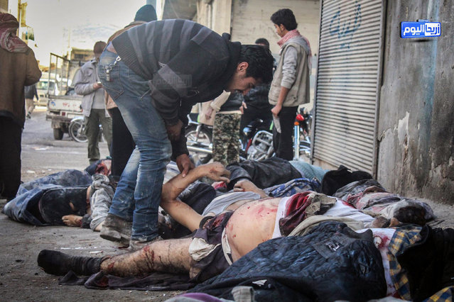 In this November 29, 2015, file photo provided by the Syrian anti-government activist group Ariha Today, which has been authenticated based on its contents and other AP reporting, a Syrian man tries to identify victims after airstrikes believed to be carried out by Russian warplanes in the center of Ariha town in the northwestern province of Idlib. (Photo by Ariha Today via AP Photo)
