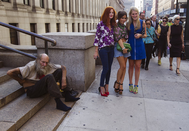 Fashionistas pose for photographs in front of a homeless man outside Moynihan Station following a showing of the Rag & Bone Spring/Summer 2013 collection during New York Fashion Week September 7, 2012. (Photo by Lucas Jackson/Reuters)