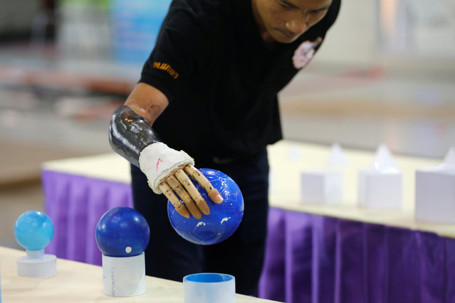 Pongchai Nakken, 31, holds a ball with his robotic hand during a robotics fair aimed at helping people with disabilities, in Bangkok, Thailand, January 30, 2017. (Photo by Chaiwat Subprasom/Reuters)