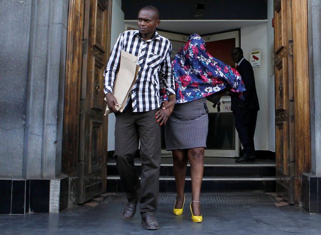 A Kenyan police officer escorts a suspect after they seized fake currency in a personal safety deposit box at the Queensway branch of Barclays Bank of Kenya, in downtown Nairobi, Kenya March 19, 2019. (Photo by Njeri Mwangi/Reuters)