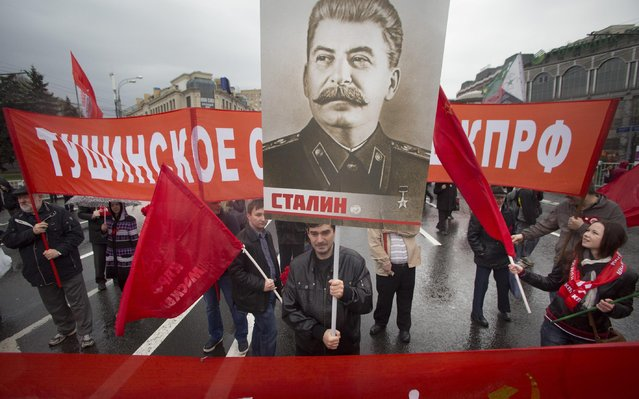 Communists carry a portrait of former Soviet leader Josef Stalin as they march along Kremlin Towers during a May Day demonstration in Moscow, Friday, May 1, 2015. (Photo by Denis Tyrin/AP Photo)