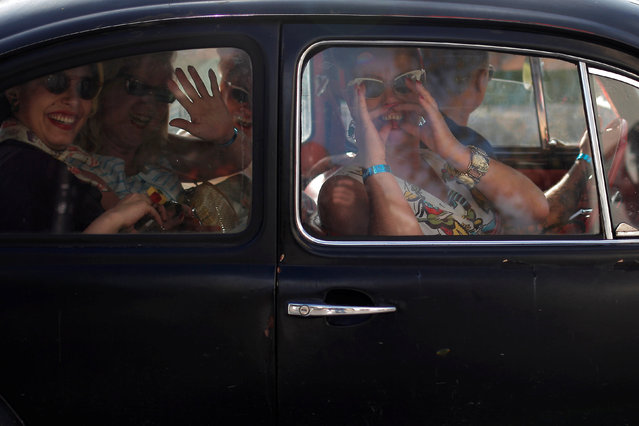 Women dressed in fifties-style outfits gesture as they sit in an old car during the 23rd Rockin' Race Jamboree International Festival in downtown Torremolinos, near Malaga, southern Spain February 4, 2017. (Photo by Jon Nazca/Reuters)