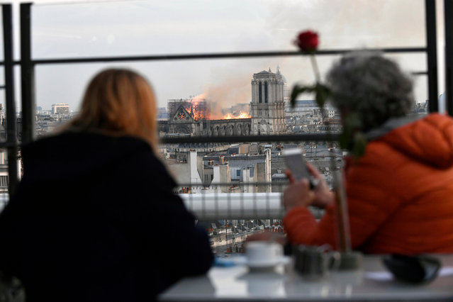 People look at the flames burning the roof of the Notre-Dame Cathedral in Paris, France, 15 April 2019. A fire started in the late afternoon in one of the most visited monuments of the French capital. (Photo by Julien de Rosa/EPA/EFE)