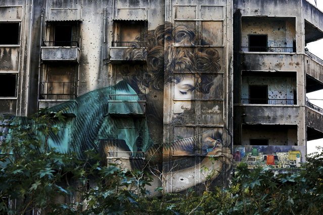 In this November 12, 2018, photo, graffiti by Cuban-American artist Jorge Rodriguez-Gerada depicting a boy is painted on a bullet riddled building on the former frontline of the 1975-1990 Lebanese civil war in downtown Beirut, Lebanon. Nearly 30 years after civil war guns fell silent, dozens of bullet-scarred, shell-pocked buildings are still standing _ testimony to a brutal conflict that raged for 15 years and took the lives of 150,000 people. (Photo by Hassan Ammar/AP Photo)