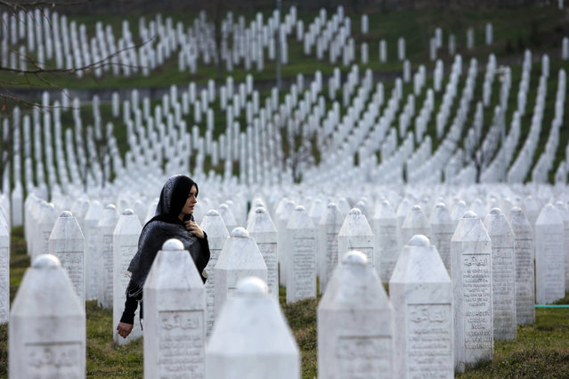 In this photo taken on Sunday, March 20, 2016, a Bosnian woman walks among gravestones at Memorial Centre Potocari near Srebrenica, Bosnia and Herzegovina. Former Bosnian Serb leader Radovan Karadzic will hear his verdict on Thursday, March 24, 2016 and prosecutors of the U.N. war crimes tribunal have called for life in prison for 11 counts of war crimes, including genocide he is accused of having masterminded during Bosnia's 1992-95 war. (Photo by Amel Emric/AP Photo)