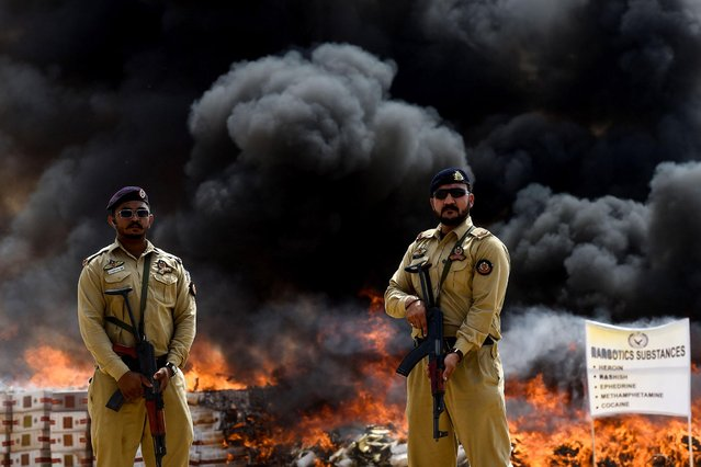 Members of the Pakistani Anti-Narcotic Force (ANF) stand guard beside a pile of burning illicit drugs smuggled in the country and seized by the Pakistan Coast Guards, on the outskirts of Karachi on April 25, 2019. (Photo by Asif Hassan/AFP Photo)