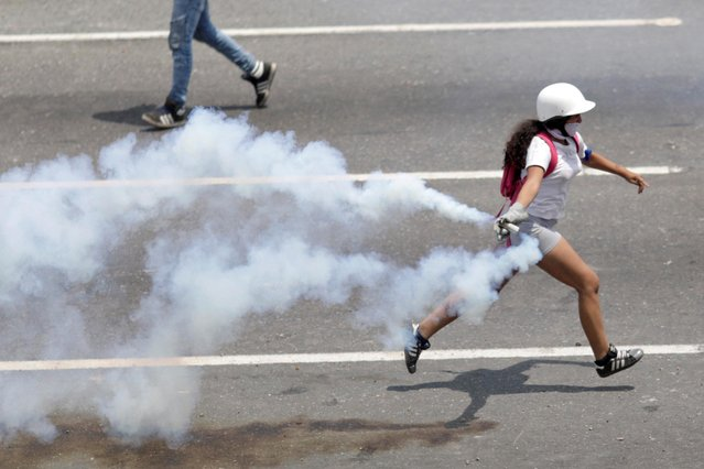 An opposition supporter runs with a tear gas canister during a rally against the government of Venezuela's President Nicolas Maduro and to commemorate May Day in Caracas, May 1, 2019. (Photo by Ueslei Marcelino/Reuters)