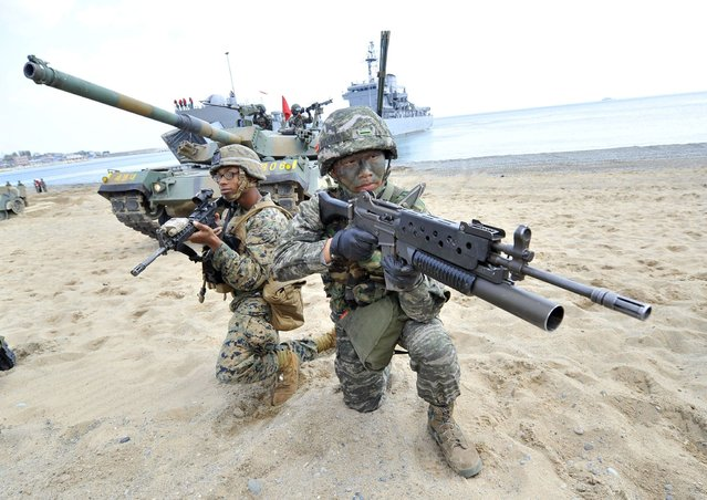 South Korean (R) and US (L) Marines take a position on the seashore during a joint landing operation by US and South Korean Marines in Pohang, 270 kms southeast of Seoul, on April 26, 2013. The US and South Korea staged a military landing exercise as the Korean peninsula was already engulfed in a cycle of escalating tensions triggered by the North Korea's nuclear test in February. (Photo by Jung Yeon-Je/AFP Photo)