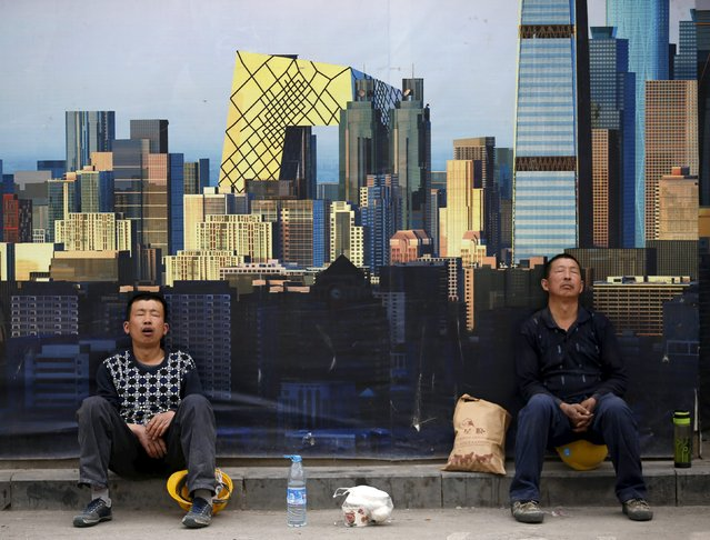 Construction workers take a nap in front of a wall of a construction site during their lunch break in Beijing, China, May 5, 2015. As growth in China's sagging economy looks on the verge of spilling below 7 percent, officials worried about a spike in unemployment are pulling out all the stops to avoid mass lay-offs. (Photo by Kim Kyung-Hoon/Reuters)