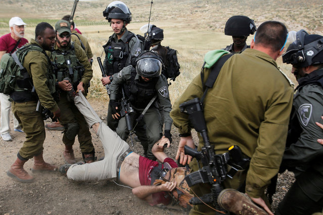 Israeli forces drag a foreign activist as they detain him during a protest against what organizers say are demolitions of Palestinian houses by Israel, in Yatta in the Israeli-occupied West Bank on May 3, 2019. (Photo by Mussa Qawasma/Reuters)