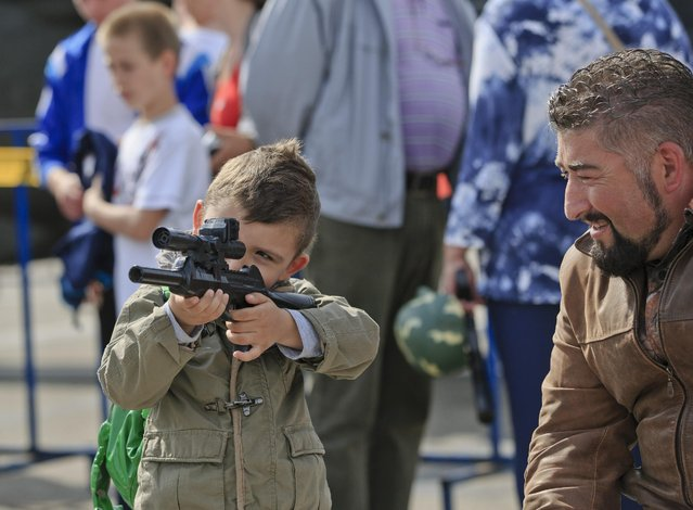 A child aims a toy weapon outside a shopping mall in Ploiesti, Romania, Wednesday, May 13, 2015. Members of the US military took part in an exercise dubbed the Cavalry March, a drive from southern Romania to a training range in the central region of Transylvania, involving 400 servicemen and 80 armored combat vehicles. (Photo by Vadim Ghirda/AP Photo)