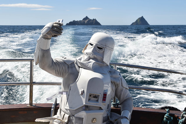 A member of the 501st Garrison dressed as a snowtrooper takes a selfie as he sails around Skellig Michael on May 4, 2019 in Portmagee, Ireland. The latest Star Wars movies such as The Last Jedi have featured the famous Skellig Michael islands situated off the coast of the small Irish fishing village. The May the Fourth Star Wars festival is taking place in the small County Kerry village for the second year running as millions of fans worldwide celebrate the science fiction series. The quiet coastal setting has seen a sharp rise in the number of tourists and fans visiting the area. (Photo by Charles McQuillan/Getty Images)