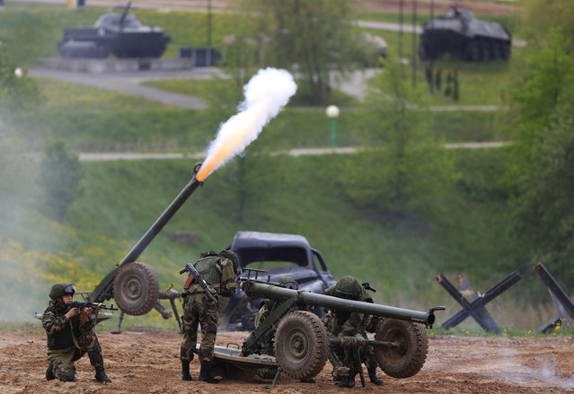 """Military show participants perform at the """"Stalin Line"""" memorial near the village of Goroshki, on the outskirts of Minsk, Belarus, Wednesday, May 15, 2019. The show is devoted to opening the 9th international exhibition of arms and military hardware, the Milex 2019. The exhibition runs from May 15 with over 170 companies and enterprises participating from different countries. (Photo by Sergei Grits/AP Photo)"""