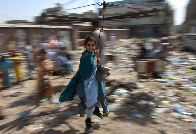In this photograph taken on February 18, 2016, Pakistani children ride on swings in the predominantly Pashtun Korangi District of Karachi. In a rundown district of Karachi, Rabia balks at a neighbour's proposal to vaccinate her children, demonstrating one of the biggest hurdles to eradicating polio in Pakistan by the end of the year: confused and frightened parents. (Photo by Asif Hassan/AFP Photo)