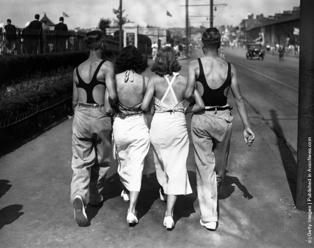 Four young people in swimming costumes walking along arm in arm at Thorpe Bay, Essex, England, 1934