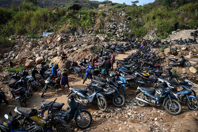 "This photo taken on May 16, 2019 shows miners arriving with equipment on motorcycles at a ruby mining site in Mogok, north of Mandalay. Burrowing deep underground, thousands of informal miners risk their lives to find gleaming red gems as a law change spurs opportunity in Myanmar's ""land of rubies"". (Photo by Ye Aung Thu/AFP Photo)"