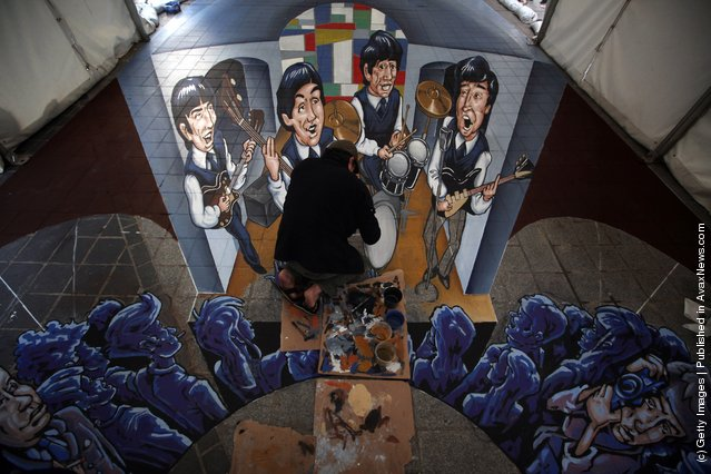 Street artist Juandres Vera puts the finishing touches to a giant 3d pavement mural of The Beatles