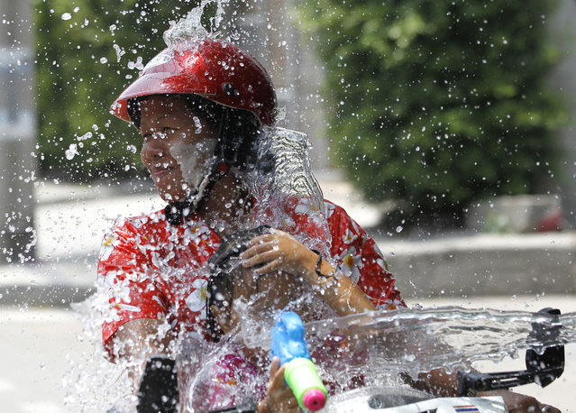 In this  April 13, 2015 file photo a woman and a girl riding on a motorbike react as a boy splashes water on them during traditional Thai New Year celebrations or Songkran water festival in Bangkok. Thailand's military government is putting a dampener on the annual nationwide water fight. Despite Thailand's worst drought in 20 years, the junta says it has no intention of limiting the virtually around-the-clock water throwing that defines the three-day Songkran festival. Instead, it has decided to impose morality measures. (Photo by Sakchai Lalit/AP Photo)