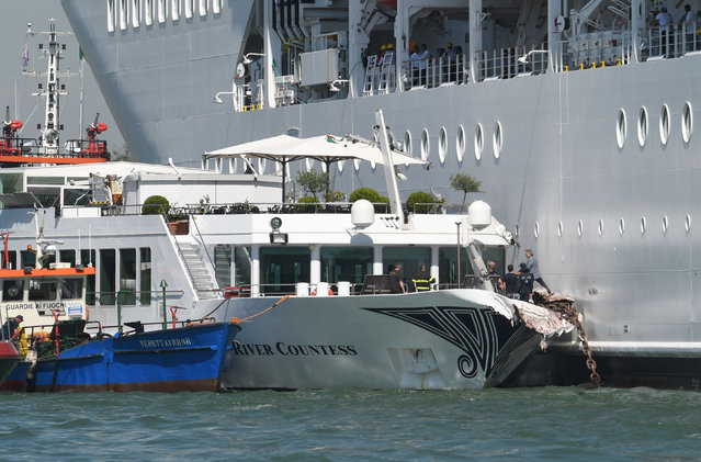 Rescuers stand onboard the damaged River Countess tourist boat after it was hit early on June 2, 2019 by the MSC Opera cruise ship (Rear) that lost control as it was coming in to dock in Venice, Italy. Tourists on land could be seen running away as the MSC Opera scraped along the dockside, its engine blaring, before knocking into the River Countess tourist boat. (Photo by Andrea Pattaro/AFP Photo)