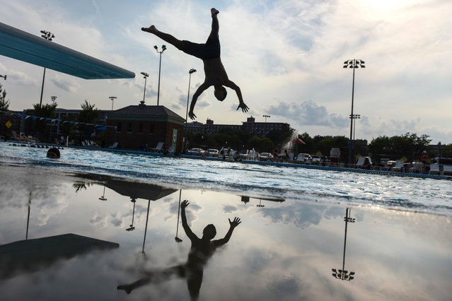 Ivan Nolia, 14, leaps off a diving board in Washington, USA on August 15, 2018. (Photo by Michael Robinson Chavez/The Washington Post)