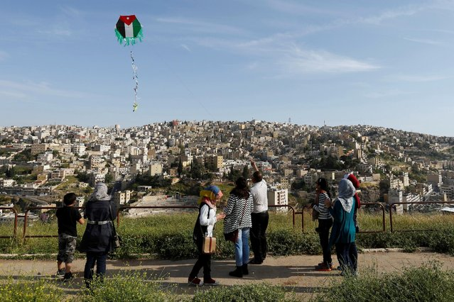 People fly kites decorated with the Jordanian national flag during an event celebrating spring at the Citadel in Amman, Jordan, April 15, 2016. (Photo by Muhammad Hamed/Reuters)
