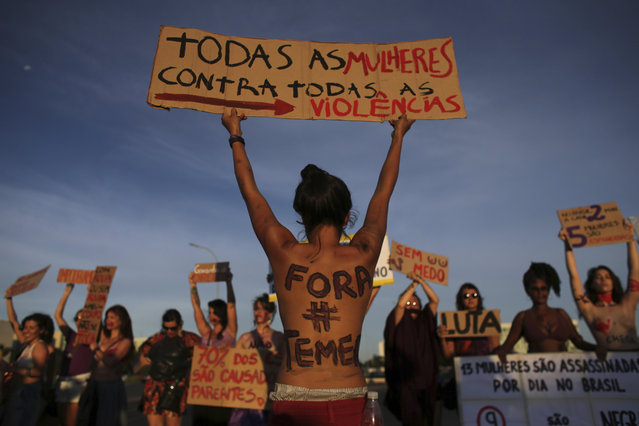 "A woman with her body painted with the Portuguese message ""Get out Temer"", referring to Brazil's President, holds up a sign that says: ""All the women against all violence"" during a protest on International Women's Day in Brasilia, Brazil, Wednesday, March 8, 2017. (Photo by Eraldo Peres/AP Photo)"