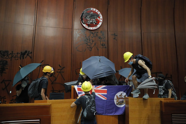 Protesters put a Hong Kong colonial flag and deface the Hong Kong logo at the Legislative Chamber after break in to protest against the extradition bill in Hong Kong, Monday, July 1, 2019. The extradition law has aroused concerns that this legislation would undermine the city's independent judicial system as it allows Hong Kong to hand over fugitives to the jurisdictions that the city doesn't currently have an extradition agreement with, including mainland China, where a fair trial might not be guaranteed. (Photo by Kin Cheung/AP Photo)