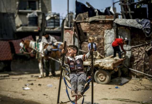 A Palestinian boy rides on a make-shift swing in an impoverished area in Beit Lahia in the northern Gaza Strip on May 22, 2019. (Photo by Mohammed Abed/AFP Photo)