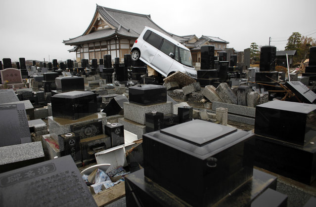 A damaged car is seen in a cemetery at an area devastated by the March 11 earthquake and tsunami, in Watari, Miyagi prefecture, April 22, 2011. (Photo by Toru Hanai/Reuters)