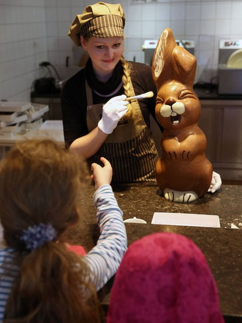 Sandra Jaeckel demonstrates a brush technique on a giant chocolate Easter bunny at Confiserie Felicitas chocolates maker in Hornow. (Photo by Sean Gallup/Getty Images)