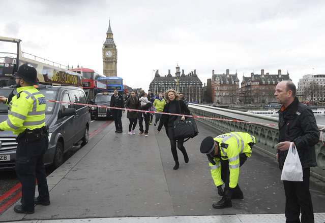 A woman ducks under a police tape after an incident on Westminster Bridge in London, Britain on Wednesday, March 22, 2017. (Photo by Toby Melville/Reuters)