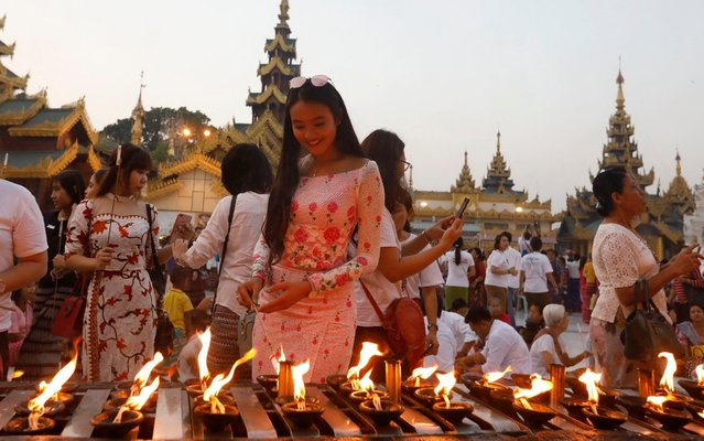 A woman lits oil light as she offers light at the Shwedagon pagoda in Yangon, Myanmar, 28 April 2019. Buddhist people arrange to offer thirty feet and twenty feet long decorated flowers and some nine thousand candle lights to Buddha at the Shwedagon pagoda. (Photo by Nyein Chan Naing/EPA/EFE/Rex Features/Shutterstock)