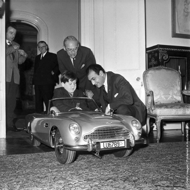 Seven-year old Ian Heggie, the son of Aston Martin's Deputy Managing Director, test drives a toy Aston Martin DB5, at the Iranian Embassy in London, 20th December 1966