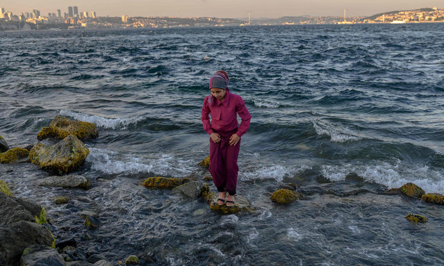 """A woman stands on rocks in the sea during the Muslim religious festival of Eid al-Adha (Feast of Sacrifice) at Sarayburnu in Eminonu district, in Istanbul, on August 13, 2019. Known as the """"big"""" festival, Eid Al-Adha is celebrated each year by Muslims sacrificing various animals according to religious traditions, including cows, camels, goats and sheep. The festival marks the end of the Hajj pilgrimage to Mecca and commemorates Prophet Abraham's readiness to sacrifice his son to show obedience to God. (Photo by Bulent Kilic/AFP Photo)"""