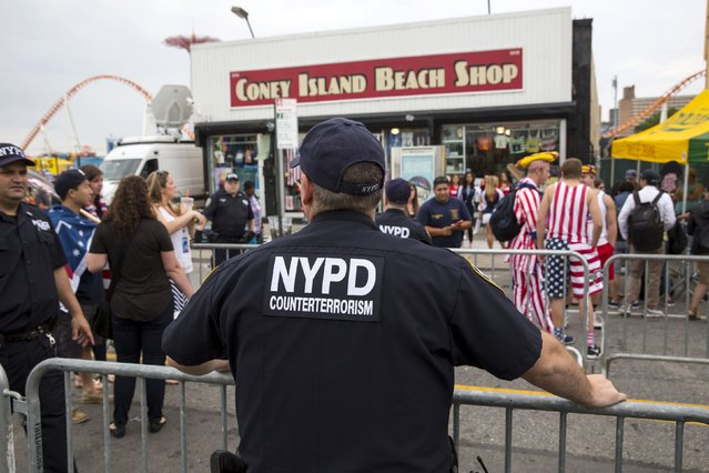 A New York Police Officer watches crowds before the annual Fourth of July 2015 Nathan's Famous Hot Dog Eating Contest in Brooklyn, New York July 4, 2015. (Photo by Andrew Kelly/Reuters)