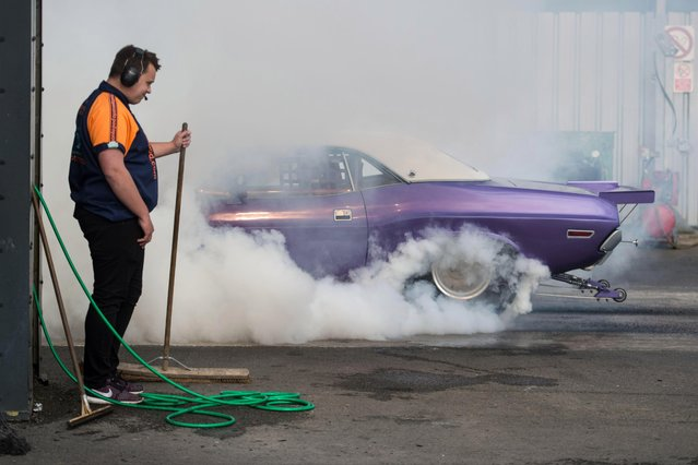 A marshal stands by as a muscle car smokes its tyres on the start line before taking part in a drag race at The Fast Show performance car event held at the Santa Pod Raceway near Wellingborough, central England on April 2, 2017. (Photo by Oli Scarff/AFP Photo)