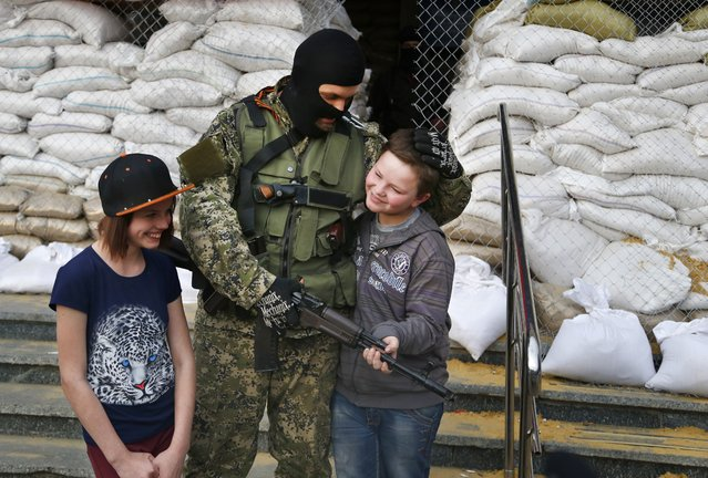 Armed Pro-Russian man poses for a photo with local children next to barricades in front of city hall in Slovyansk, eastern Ukraine, Monday, April 21, 2014. The self-proclaimed mayor of Slovyansk in eastern Ukraine is appealing to Russia to send in peacekeeping troops after a shootout at a checkpoint near the city manned by pro-Russia insurgents. (Photo by Sergei Grits/AP Photo)