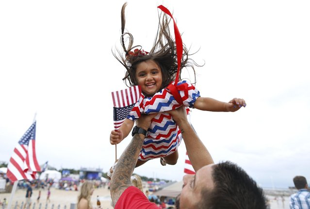 A father players with his daughter at Destination America's Red, White & You event, Saturday, July 4, 2015, in Waveland, MS. (Photo by Jonathan Bachman/AP Images for Discovery Communications)
