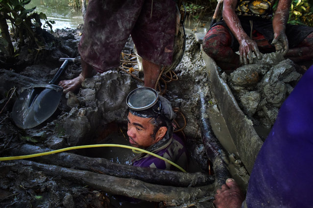 Christian Balderosdasco, 31, is being pulled up a mud pit after diving for 3 hours to look for gold on March 22, 2017 in Paracale, Philippines. (Photo by Jes Aznar/Getty Images)