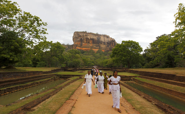 Sigiriya: Women leave Sigiriya, an ancient rock fortress and palace ruin, in Matale District, east of Colombo, June 20, 2010. (Photo by Andrew Caballero-Reynolds/Reuters)