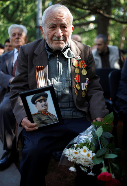 A World War Two veteran Nikoloz Nozadze, 91, holds a portrait of Joseph Stalin as he attends Victory Day commemorations in Tbilisi, Georgia, May 9, 2016. (Photo by David Mdzinarishvili/Reuters)