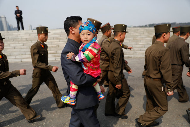 A man carries a child as people arrive at the flower exhibition marking the 105th birth anniversary of the country's founding father, Kim Il Sung in Pyongyang, North Korea April 16, 2017. (Photo by Damir Sagolj/Reuters)