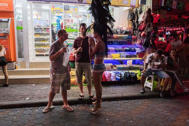 This photo taken on March 29, 2017 shows two foreign tourists (L) standing in front of a stall selling handbags in Walking Street in Pattaya. (Photo by Roberto Schmidt/AFP Photo)