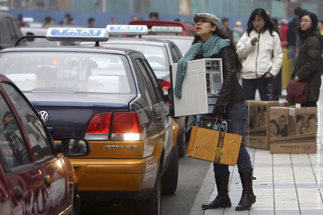 A girl tries to open the door of a taxi as she holds her assembled personal computer in front of an electronics city at Beijing's main computer district in Zhongguancun